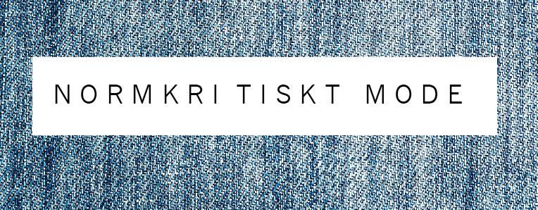på bilden står det normkritiskt mode i svart text  på vit bakgrund. Bakom texten syns blått jeanstyg