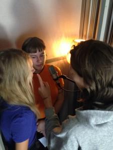 bilden visar en inspelningsstudio med tre personer som sitter och talar in manus framför en mikrofon