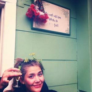 bilden visar Sofia som sitter med ett snapsglas i handen. Sofia har blont hår och ler mot kameran.